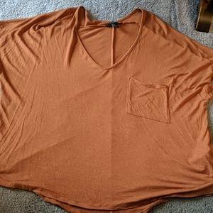 Pumpkin color scoop neck blouse with a pocket